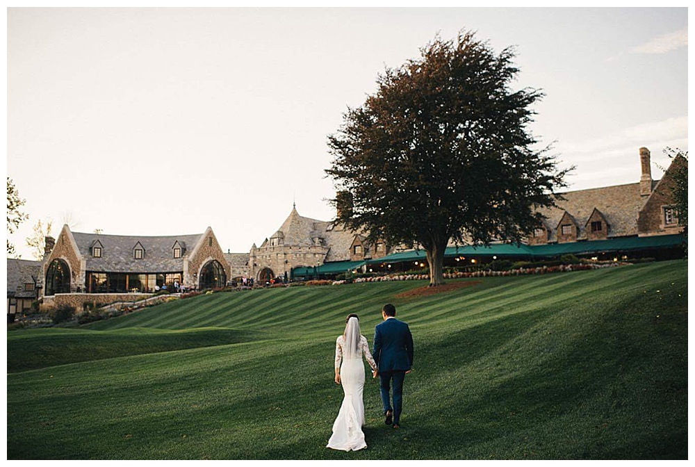 The happy couple hold hands walking up a hill at their outdoor venue with the bride's long sleeve lace wedding gown and veil on display with the groom's blue suit -Ayres Photography
