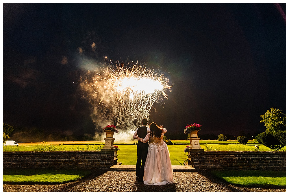 The bride and groom look at fireworks in their Buffalo custom-made pieces.