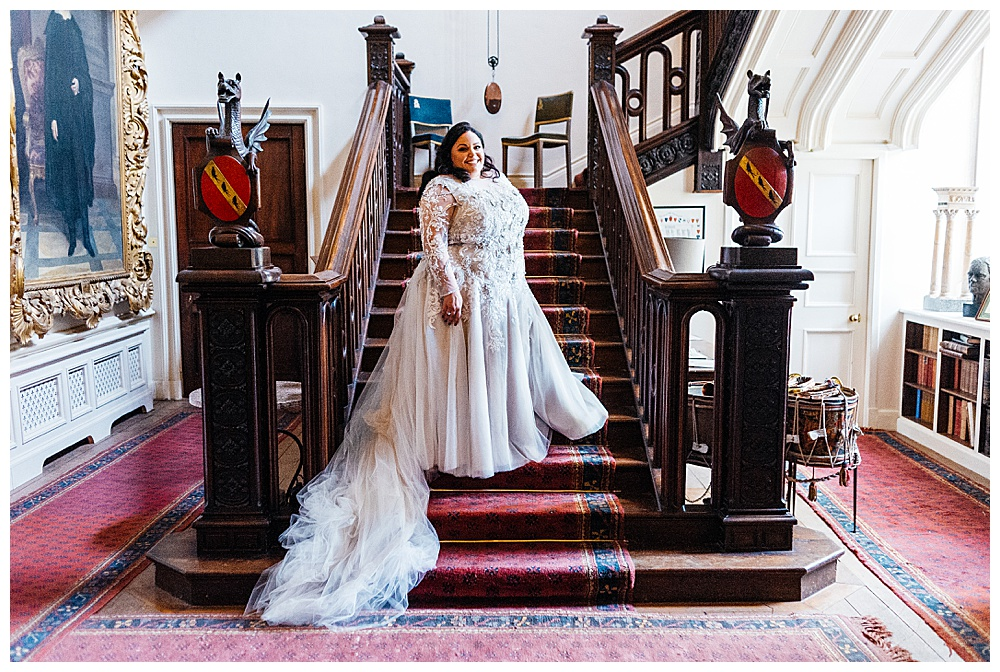 Our Anatomy bride in her custom soft purple lace wedding dress posing on a staircase for her destination wedding.