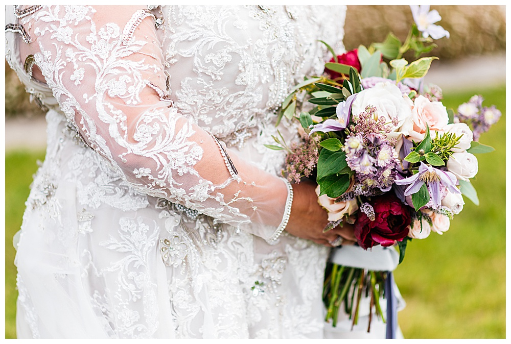 A close up of the soft purple lace appliqué and floral bouquet outside of the Irish castle where the bride married her groom in a destination wedding.