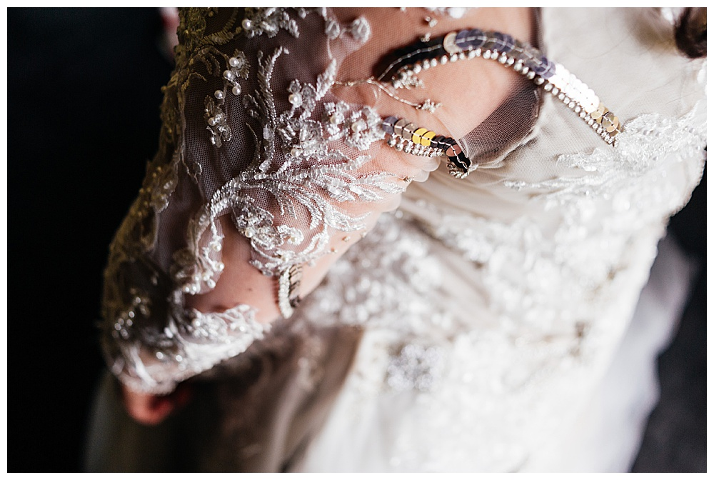 Closeup of the sleeves showing the ace and silver trim detail of the custom wedding dress.