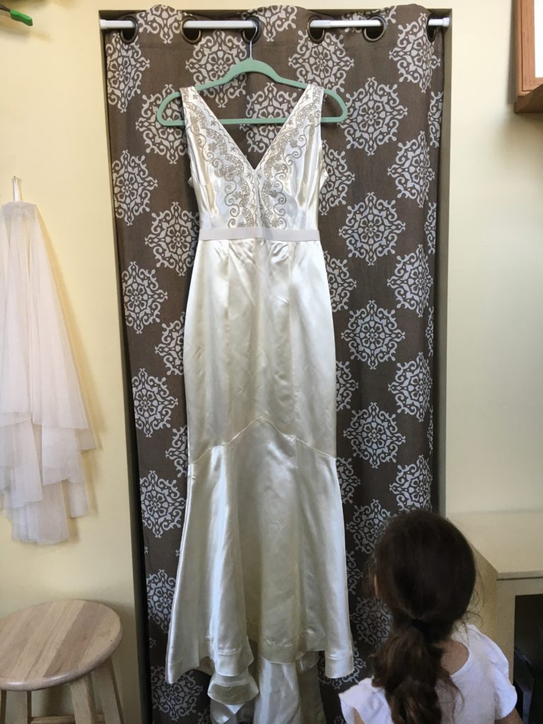 The vintage wedding dress reconstruction hangs on display in the showroom.
