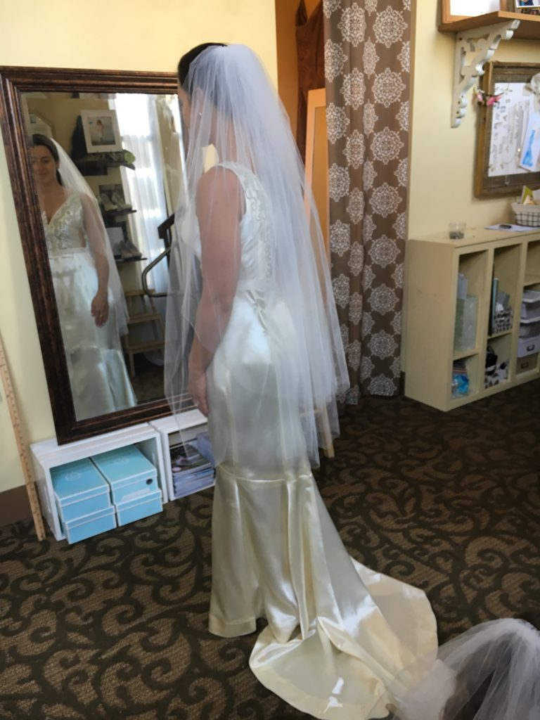 Our bride faces the mirror and tries on her vintage wedding dress reconstruction.