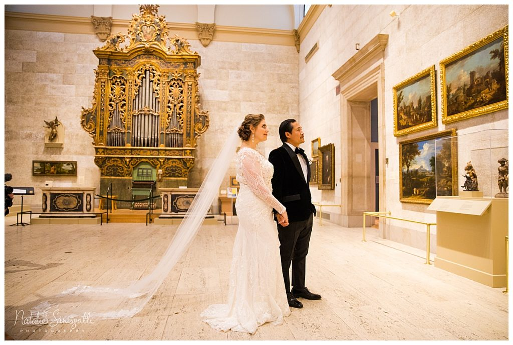 the couple look at artwork on display as a sideview of the bride's custom geometric wedding dress is shown