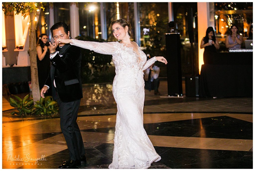 The Rochester bride and groom on the dance floor getting ready to salsa dance in her custom geometric wedding dress
