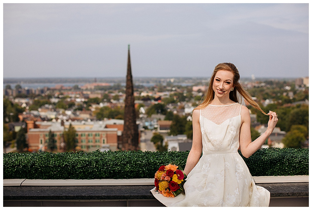 A redheaded model poses on the roof of 500 Pearl with a Blossoms N Treasures red and orange floral bouquet for a retro styled shoot.
