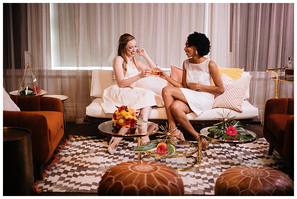 A redheaded model with fair skin wearing a white Made by Anatomy custom wedding gown cheers a young black woman also wearing a custom Made by Anatomy wedding dress in a retro styled shoot at 500 Pear in Buffalo, NYl.