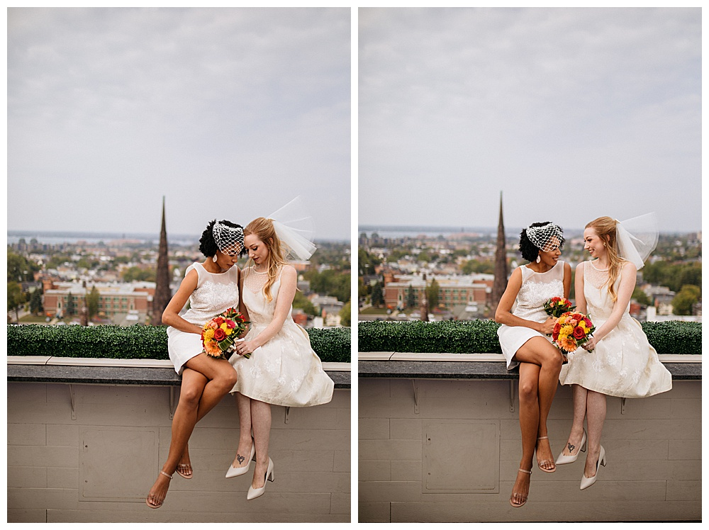 Two women poe cuddled up to each other sitting on the 500 Pearl rooftop ledge in vintage looking Made by Anatomy custom wedding dresses, each holding red and orange bouquets for a retro styled shoot.